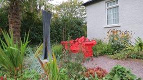 Rote Bank in einem Garten stockfotos
