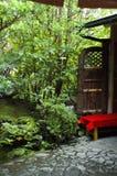 Rote Bank vor grünem Laub Stockbilder