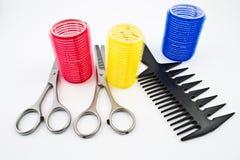 Rote, blaue und gelbe Lockenwickler mit Scheren für das Haar, das mit Kamm verdünnt und schneidet Stockbilder