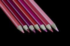 7 rote Bleistifte - schwarzer Hintergrund Stockfotografie