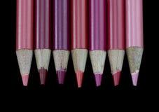7 rote Bleistifte - schwarzer Hintergrund Stockfotos