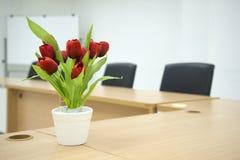 Rote Blume auf Konferenzzimmertabelle Stockfotos