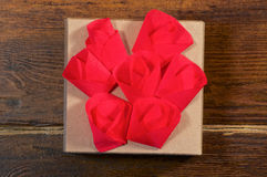 Rote Blumen über Geschenkboxnahaufnahme Stockbild