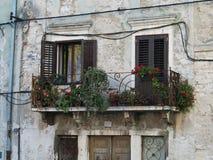 Rote Blumen auf einem alten Balkon Alte Straße einer Kleinstadt, Istria, Kroatien stockfotos