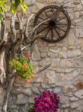 Rote Blumen in der künstlerischen Blumenanordnung mit Wagenrad lizenzfreie stockfotos