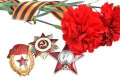 Rote Blumen gebunden mit St- Georgeband, Bestellungen des großen patriotischen Krieges Lizenzfreies Stockfoto