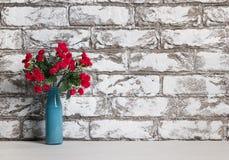Rote Blumen im Vase auf dem Tisch auf Schwarzweiss-Backsteinmauerhintergrund Stockfotografie
