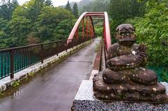 Rote Bogenbrücke und alte Statue mit Fisch- und Münzenspenden Lizenzfreies Stockfoto