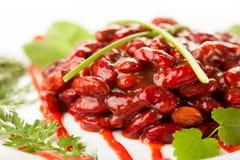 Rote Bohnen in der Tomatensauce auf einem Teller Lizenzfreie Stockfotos