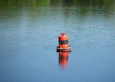 Rote Boje auf ruhigem Fluss mit dem Stillstehen auf ihr duckt O Lizenzfreie Stockfotografie