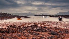 Rote Boote auf der Küste bei Ebbe in Schottland Lizenzfreies Stockbild