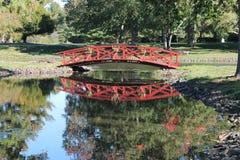 Rote Brücke über ruhigem Strom Lizenzfreie Stockfotografie
