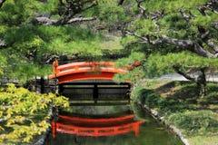 Rote Brücke über Strom des Gartens Stockbilder