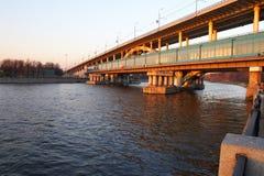 Rote Brücke und blauer Fluss. Stockfotos