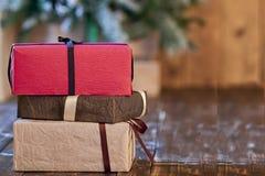 Rote, braune und sandige gelbe Weihnachtsgeschenke verziert mit Band und Bögen auf Holztisch Stockfotos