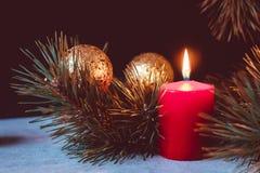 Rote brennende Kerze eines Einführungskranzes mit Tannenzweigen und goldenen Weihnachtsbällen auf einem schwarzen Hintergrund stockbild