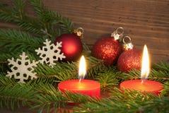 Rote brennende Kerzen mit Weihnachtsdekoration Stockbild