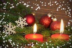 Rote brennende Kerzen mit Weihnachtsdekoration Lizenzfreie Stockbilder