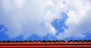 Rote Dachgesimse im Hintergrund des blauen Himmels Stockfotografie
