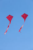 Rote Drachen, die in einen blauen Himmel fliegen Lizenzfreie Stockfotografie