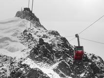 Rote Drahtseilbahn im Hochgebirge Stockbilder