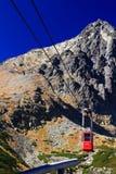 Rote Drahtseilbahn kommt in Skalnate-pleso von Lomnicky-Spitze an Stockbild