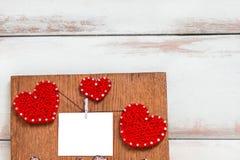 Rote drei Herzen und eine kleine weiße Karte auf einer braunen Holzverkleidung stockbild