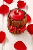 Rote duftende Kerze verziert mit Zimtstangen Rosen-Blumenblätter a Lizenzfreies Stockbild