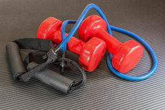 Rote Dummkopfgewichte und Widerstandbänder, die auf einem schwarzen Yoga liegen Stockbilder