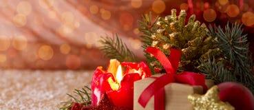 Rote Einführungskerze und Weihnachtsgeschenk Stockfotos