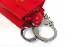 Rote Einkaufstasche mit Gag und der Handschelle Stockbild