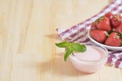 Rote Erdbeere auf einer Untertasse, stehend auf einer Tischdecke Lizenzfreies Stockfoto