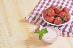 Rote Erdbeeren auf einer Untertasse, stehend auf einem Holztisch Stockfotos