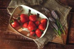 Rote Erdbeeren auf Holztisch mit den fiolet Sommerblumen, getont stockfotografie