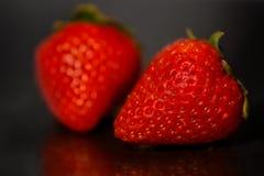 Rote Erdbeeren auf schwarzem glattem Hintergrund mit Reflexion Lizenzfreies Stockfoto