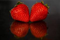 Rote Erdbeeren auf schwarzem glattem Hintergrund mit Reflexion Lizenzfreie Stockbilder