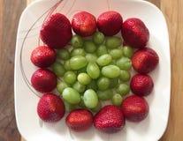 Rote Erdbeeren und grüne Trauben Stockbilder