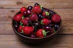 Rote Erdbeeren und reife Kirschen auf einem Holztisch, Sommer pho Lizenzfreie Stockfotos