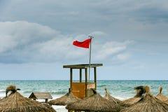 Rote Fahne über dem Strand Stockbilder