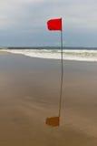 Rote Fahne auf dem Strand Stockbild