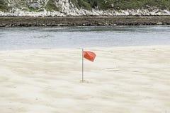 Rote Fahne auf dem Strand Lizenzfreie Stockfotografie