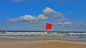 Rote Fahne auf dem Strand Stockfoto
