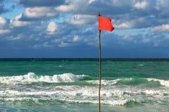 Rote Fahne auf dem Strand Stockfotos