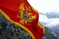 Rote Fahne auf Hintergrund von Bergen Montenegro Lizenzfreie Stockfotos