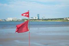 Rote Fahne, die auf die Küste wellenartig bewegt Lizenzfreies Stockbild