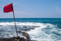 Rote Fahne, die im Wind, Meerblick flattert Stockfotos