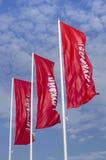Rote Fahne drei gegen den Hintergrund eines bewölkten Himmels Lizenzfreies Stockfoto