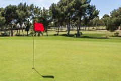 Rote Fahne im Loch auf einem grünen Golffeld Stockbilder