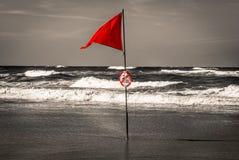 Rote Fahne im Ozean in der selektiven Farbe B&W während des Brandungswettbewerbs, Lacanau, Frankreich lizenzfreie stockfotografie
