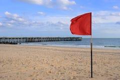 Rote Fahne am Strand Stockfotos